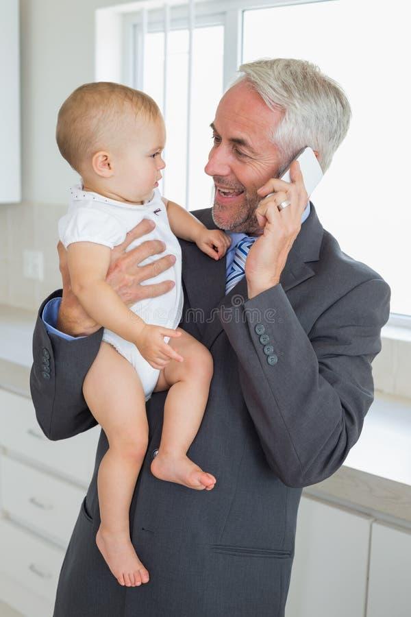 Uomo d'affari sorridente che tiene il suo bambino di mattina prima del lavoro fotografie stock