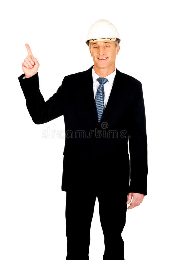 Uomo d'affari sorridente con il casco che indica su immagini stock