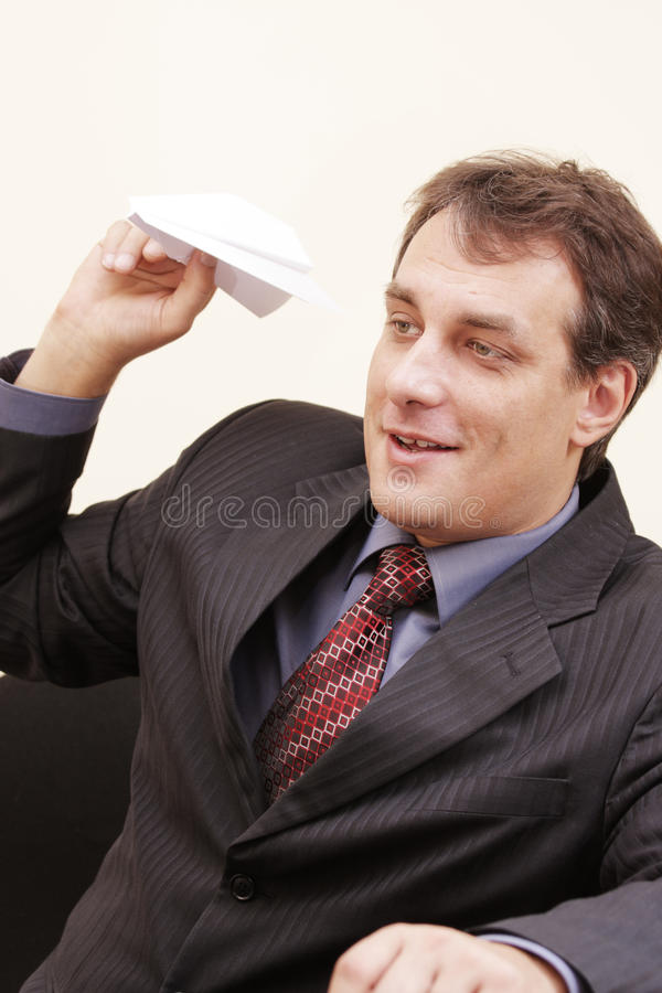 Uomo d'affari sorridente con l'aereo di carta fotografia stock libera da diritti