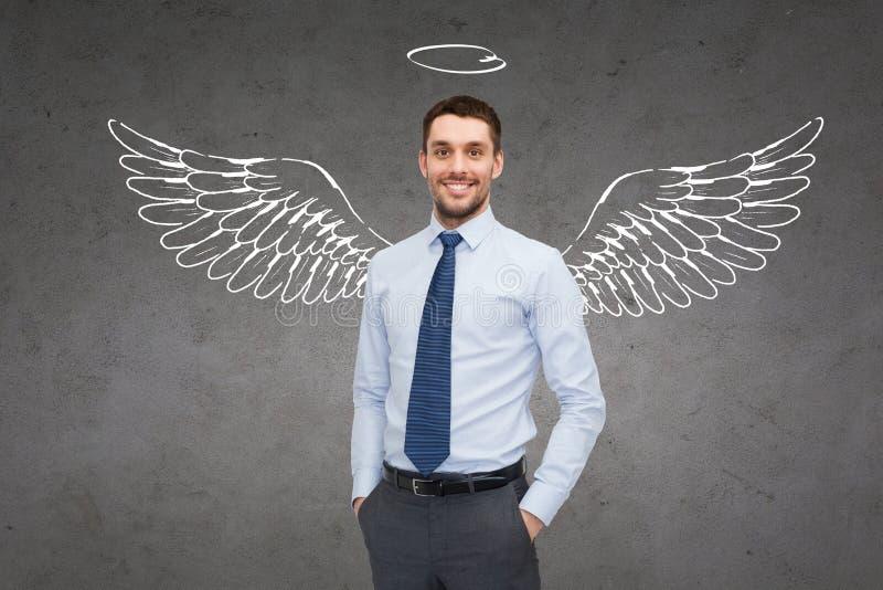 Uomo d'affari sorridente con le ali e nimbus di angelo fotografia stock libera da diritti