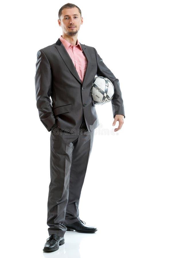 Uomo d'affari sorridente con un calcio fotografie stock