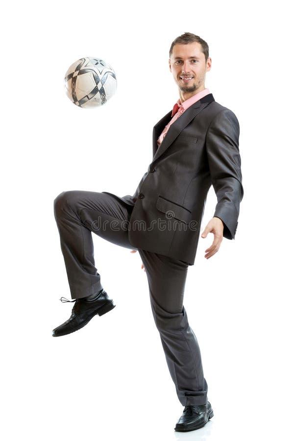 Uomo d'affari sorridente con un calcio fotografie stock libere da diritti