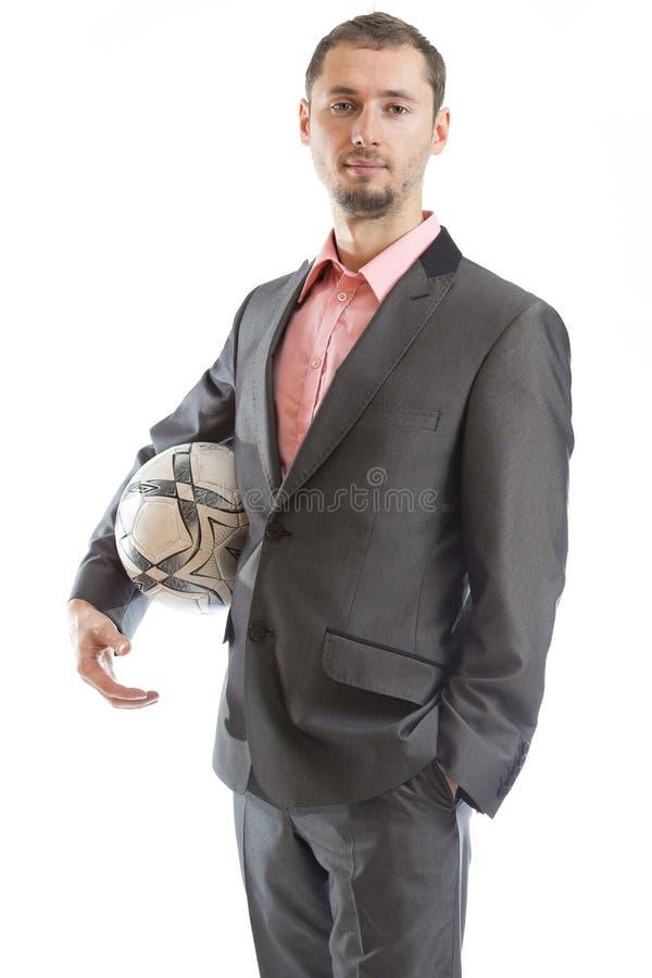 Uomo d'affari sorridente con un calcio fotografia stock libera da diritti