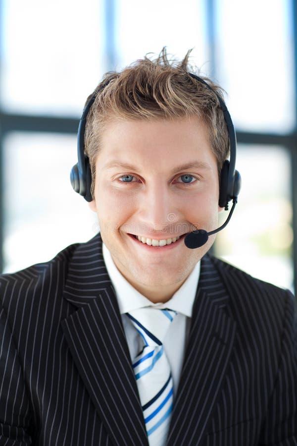 Uomo d'affari sorridente con una cuffia avricolare sopra immagine stock