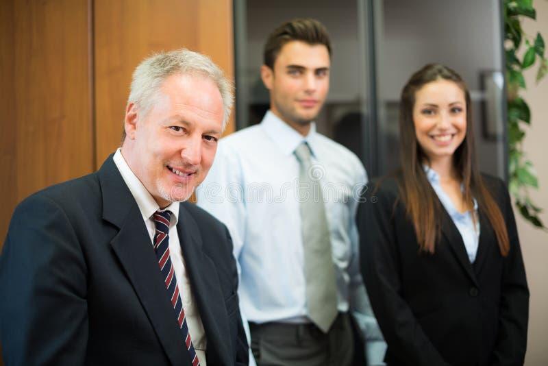 Uomo d'affari sorridente davanti ai suoi colleghi fotografia stock libera da diritti