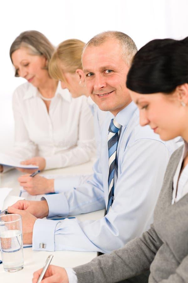 Uomo d'affari sorridente dietro lo scrittorio nel corso della riunione fotografie stock libere da diritti