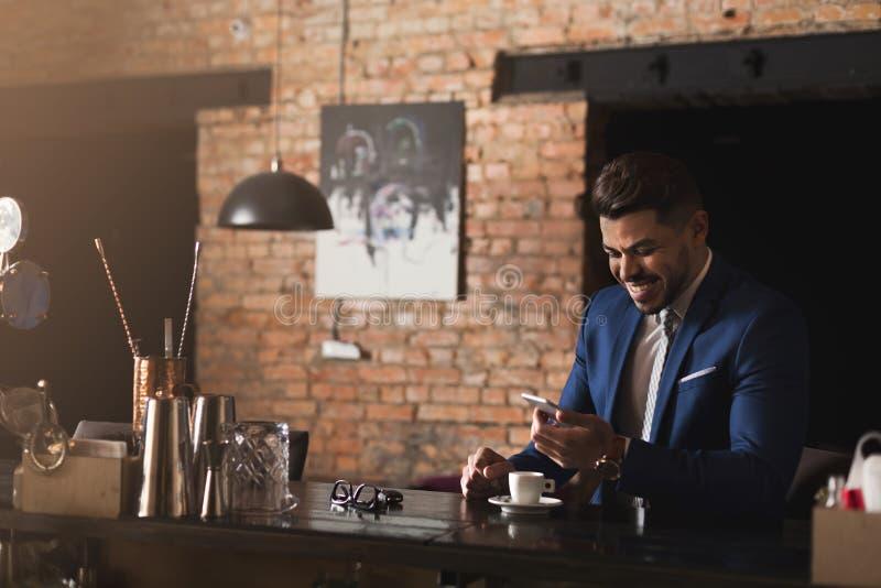 Uomo d'affari sorridente facendo uso dello smartphone alla barra immagini stock libere da diritti
