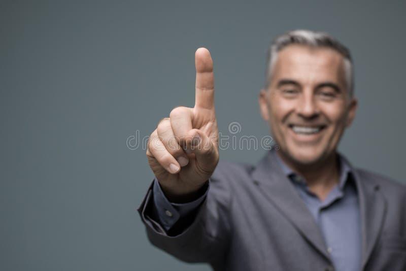 Uomo d'affari sorridente facendo uso di un'interfaccia virtuale immagine stock