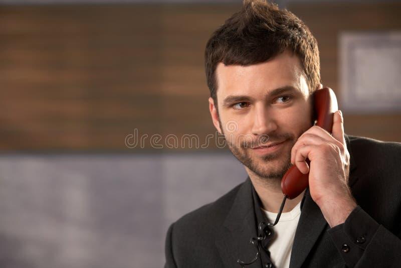 Uomo d'affari sorridente sulla chiamata fotografia stock