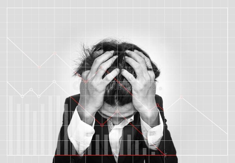 Uomo d'affari sottolineato, con i grafici commerciali discendenti Il mercato azionario di guasto e l'investimento aziendale di pe immagini stock libere da diritti
