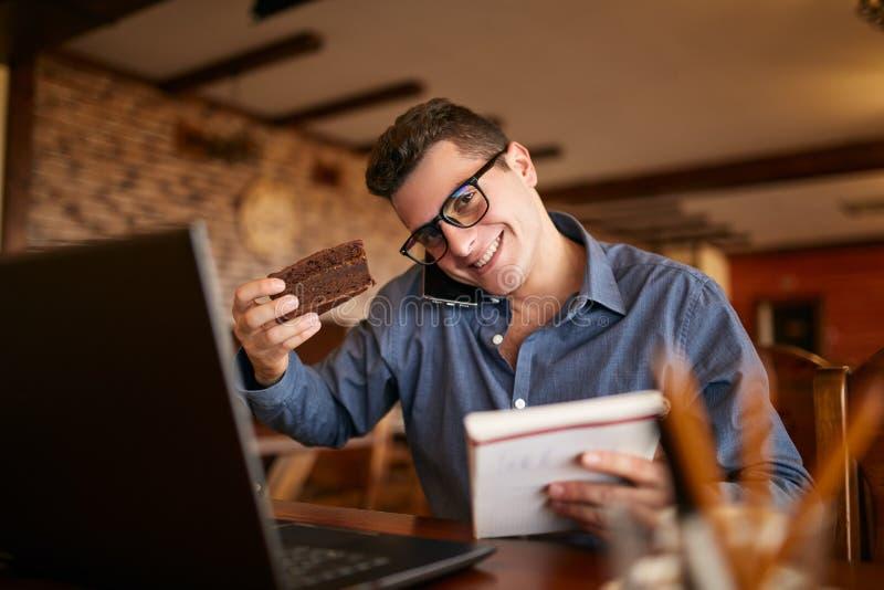 Uomo d'affari sovraccarico che parla sul cellulare che lo tiene con la spalla, leggendo le scritture in taccuino, mangiante un do fotografie stock libere da diritti
