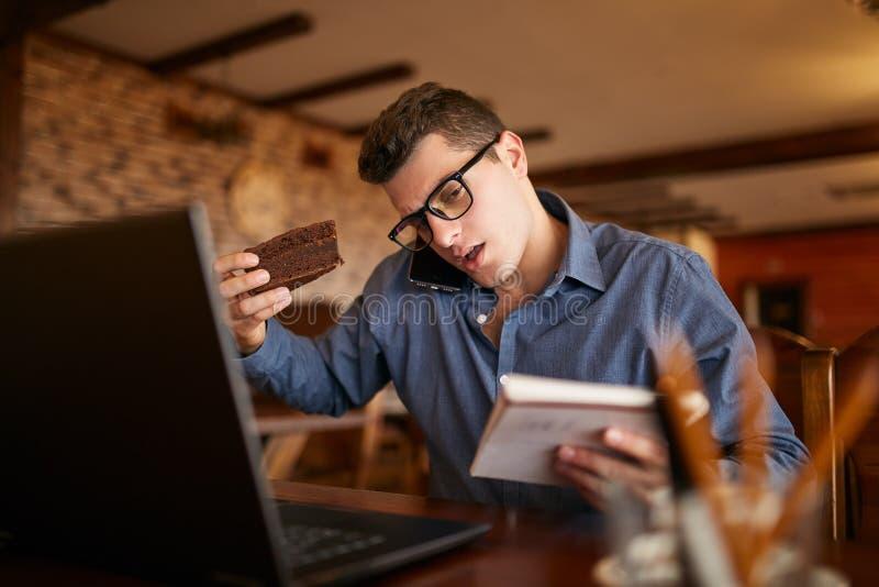 Uomo d'affari sovraccarico che parla sul cellulare che lo tiene con la spalla, leggendo le scritture in taccuino, mangiante un do immagine stock libera da diritti