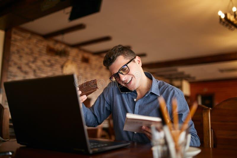 Uomo d'affari sovraccarico che parla sul cellulare che lo tiene con la spalla, leggendo le scritture in taccuino, mangiante un do fotografia stock libera da diritti