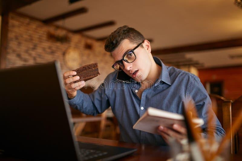 Uomo d'affari sovraccarico che parla sul cellulare che lo tiene con la spalla, leggendo le scritture in taccuino, mangiante un do fotografia stock
