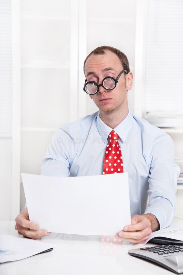 Uomo d'affari sovraccarico e stanco con i vetri che legge allo scrittorio immagine stock libera da diritti
