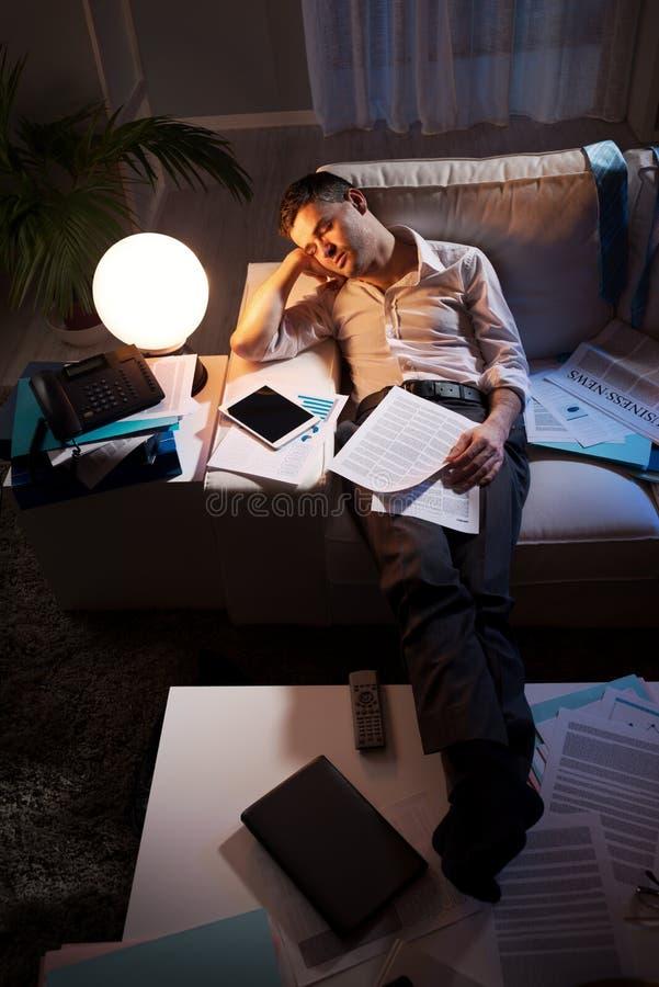 Uomo d'affari sovraccarico sul sofà fotografie stock libere da diritti