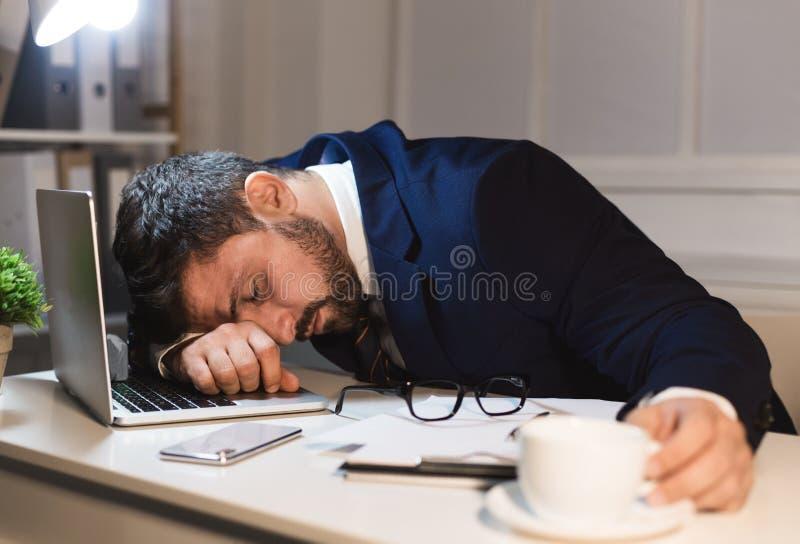 Uomo d'affari stanco che dorme sul computer portatile nell'ufficio fotografia stock libera da diritti