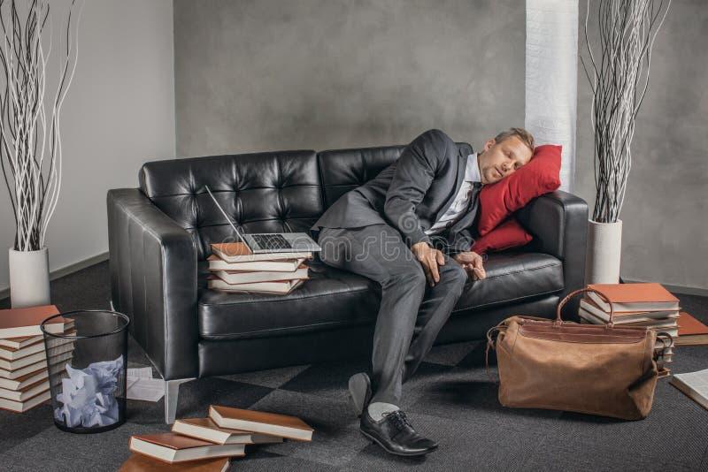 Uomo d'affari stanco che dorme sullo strato fotografia stock libera da diritti