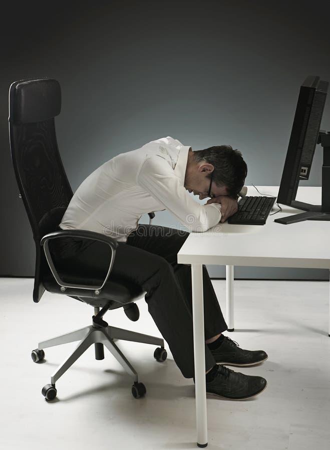 Uomo d'affari stanco che ha un pelo sullo scrittorio fotografia stock
