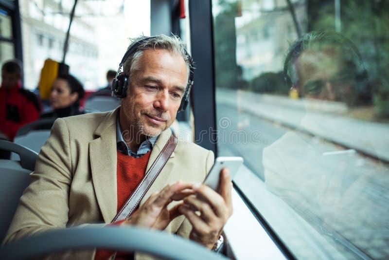 Uomo d'affari stanco maturo con i heaphones e smartphone che viaggia in bus in città fotografia stock libera da diritti