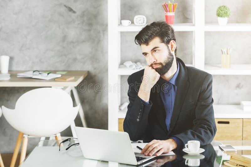 Uomo d'affari stanco nel luogo di lavoro immagine stock