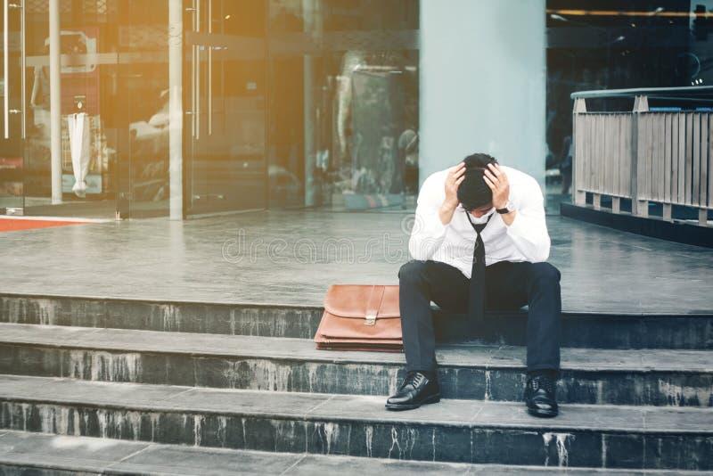 Uomo d'affari stanco o sollecitato disoccupato che si siede sul passaggio pedonale immagine stock