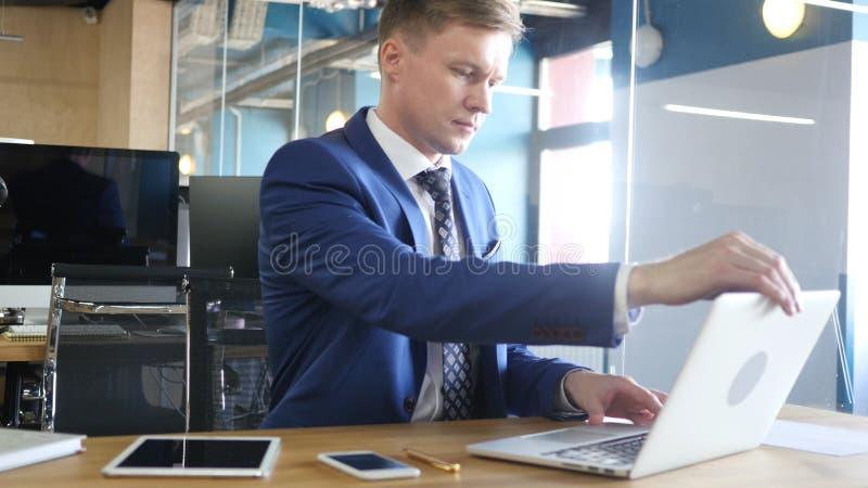 Uomo d'affari Starting il suo giorno lavorativo, computer portatile di apertura immagine stock