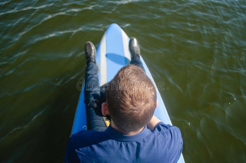 Uomo d'affari su un surf, su un giovane in una camicia e sulle scarpe che galleggiano sul fiume su un paddleboard, il concetto di fotografia stock