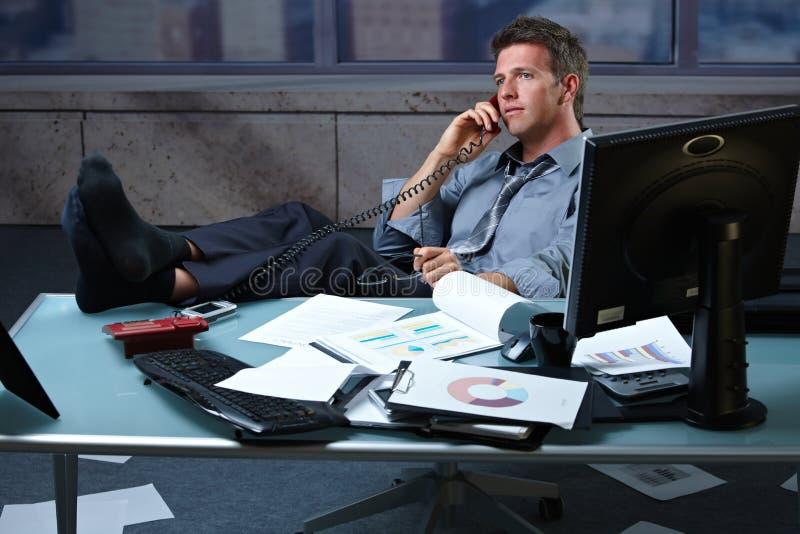 Uomo d'affari sui piedi di chiamata in su sulla scrivania fotografie stock libere da diritti