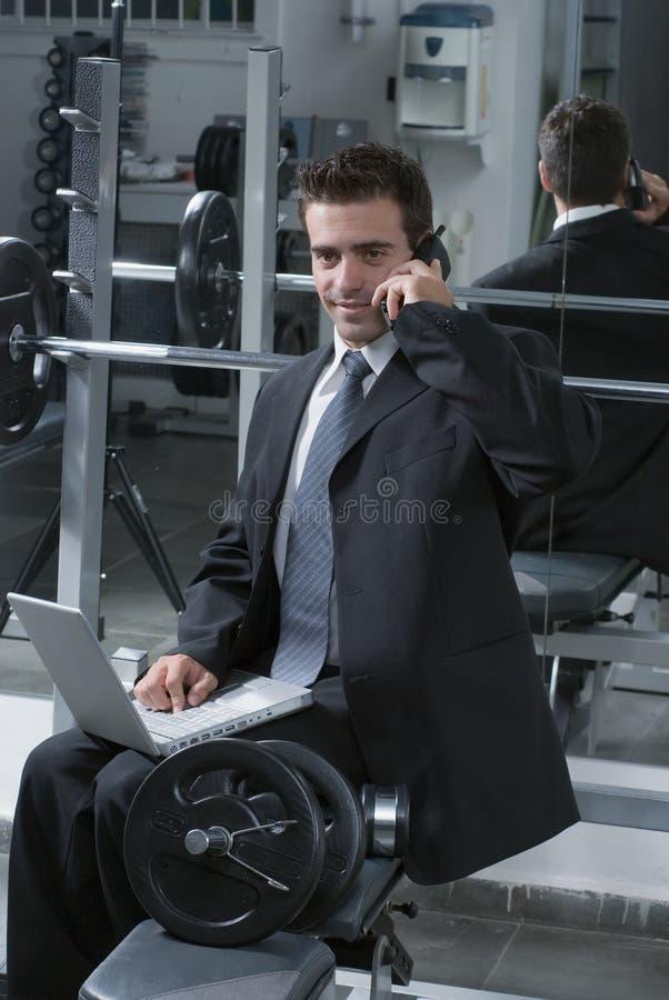 Uomo d'affari sul telefono a ginnastica fotografia stock libera da diritti