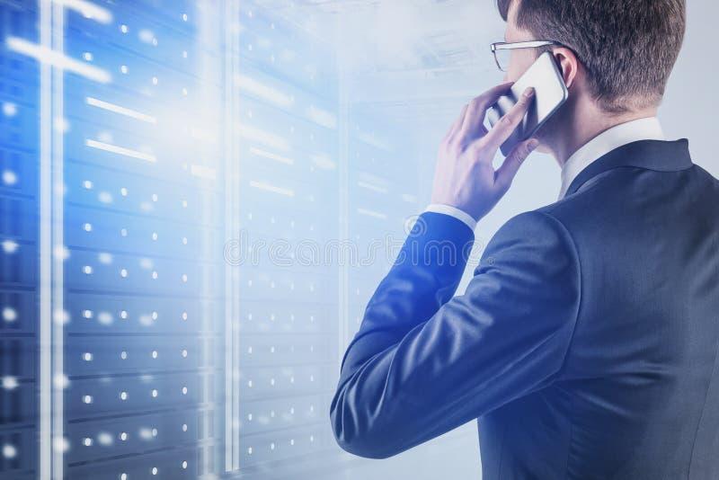 Uomo d'affari sul telefono nella stanza del server immagini stock libere da diritti