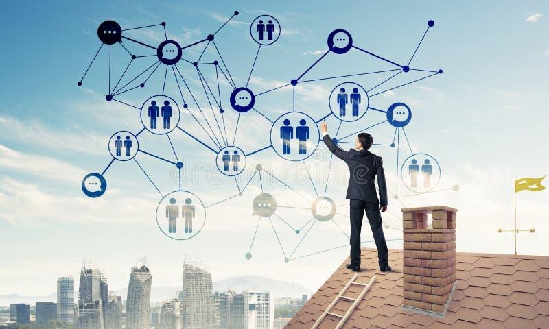 Uomo d'affari sul tetto della casa che presenta rete e collegamento c immagini stock libere da diritti