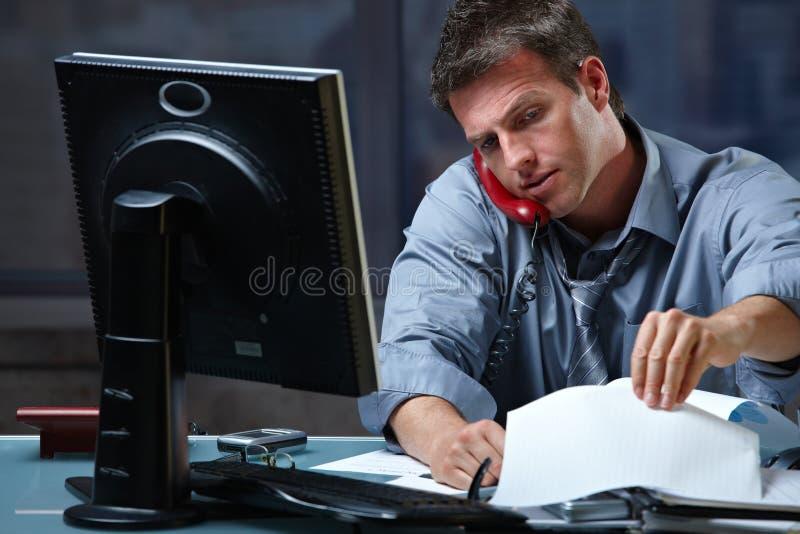 Uomo d'affari sulla chiamata in fuori orario immagini stock