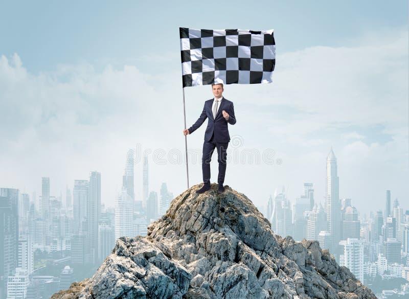 Uomo d'affari sulla cima di una città che raggiunge il suo scopo fotografia stock