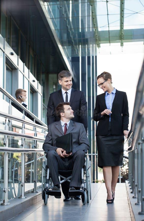 Uomo d'affari sulla sedia a rotelle e sui suoi colleghe immagini stock libere da diritti