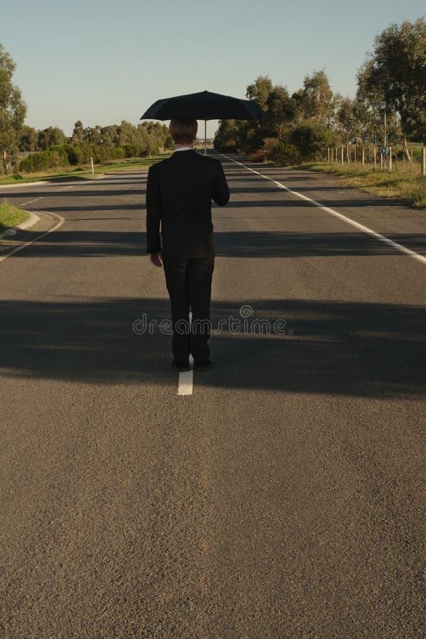 Uomo d'affari sulla strada con l'ombrello immagini stock libere da diritti