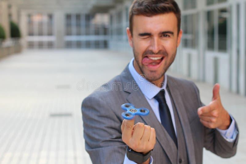 Uomo d'affari sveglio che gioca con un filatore della mano fotografie stock