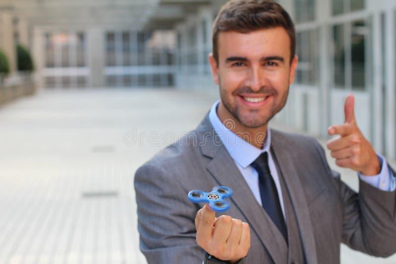 Uomo d'affari sveglio che gioca con un filatore della mano immagine stock libera da diritti