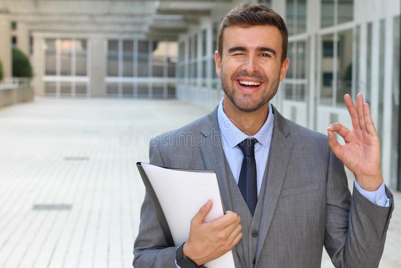 Uomo d'affari sveglio che sbatte le palpebre vicino su e che dà un segno GIUSTO con la mano fotografie stock
