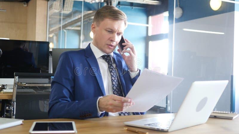 Uomo d'affari Talking sul telefono e sui documenti e sulle informazioni di discussione immagini stock