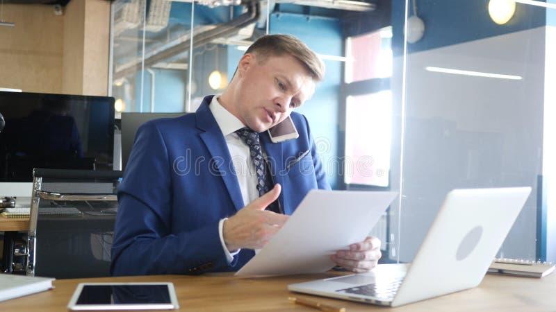 Uomo d'affari Talking sul telefono e sui documenti e sulle informazioni di discussione fotografia stock libera da diritti