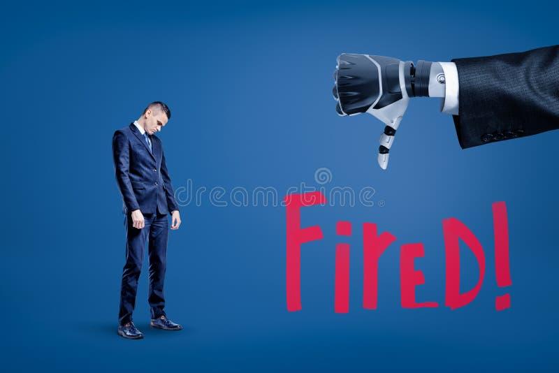 Uomo d'affari triste che guardano giù e grande primo piano della mano del robot che fa i pollici giù con il titolo infornato sott immagini stock
