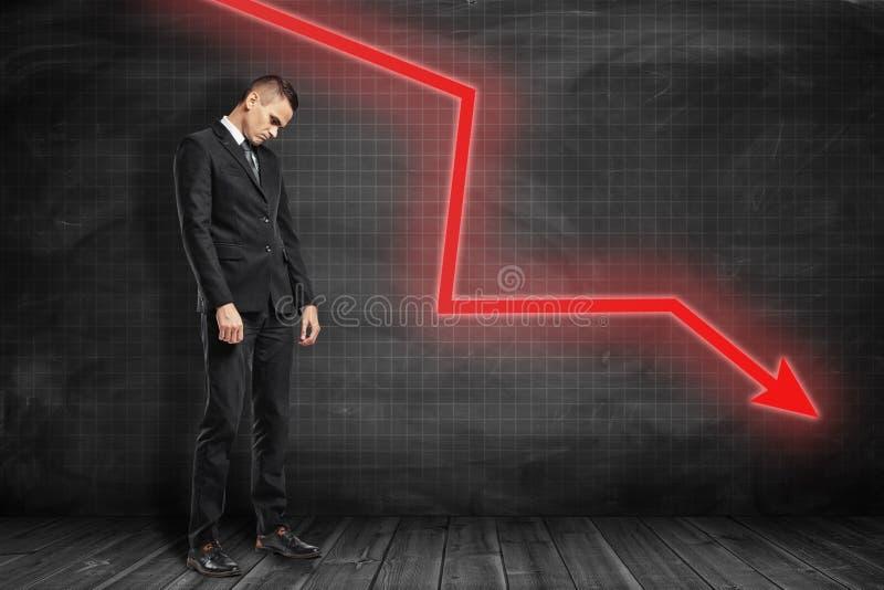 Uomo d'affari triste con la freccia rossa che va giù sul fondo nero fotografia stock