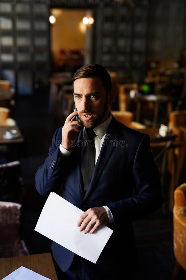 Uomo d'affari turbato che ascolta il collega sul telefono fotografia stock