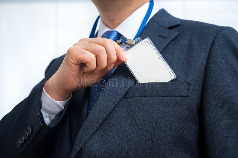 Uomo d'affari in tuta con una carta d'identità vuota o una carta di nome su un cortile di un'esposizione o di una conferenza immagine stock