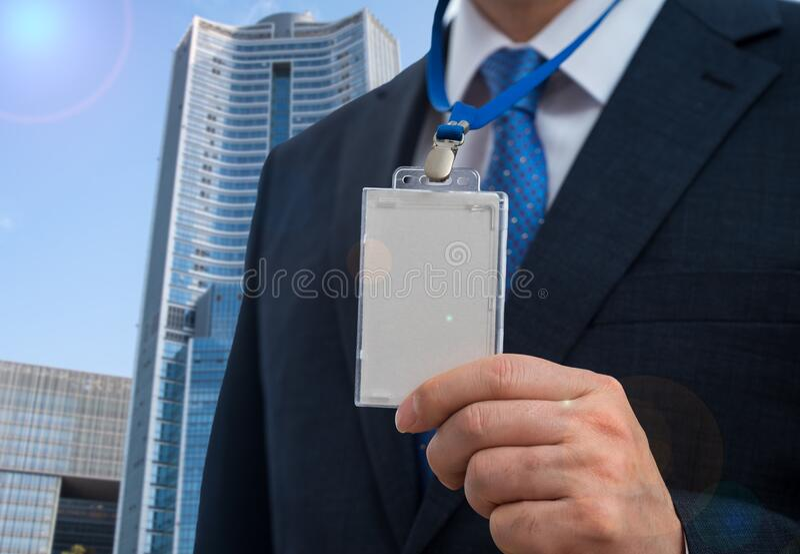 Uomo d'affari in tuta con una carta d'identità vuota o una carta di nome su un cortile di un'esposizione o di una conferenza fotografia stock libera da diritti