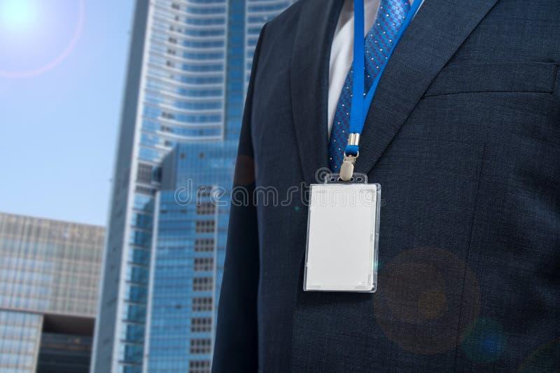 Uomo d'affari in tuta con una carta d'identità vuota o una carta di nome su un cortile di un'esposizione o di una conferenza fotografie stock libere da diritti
