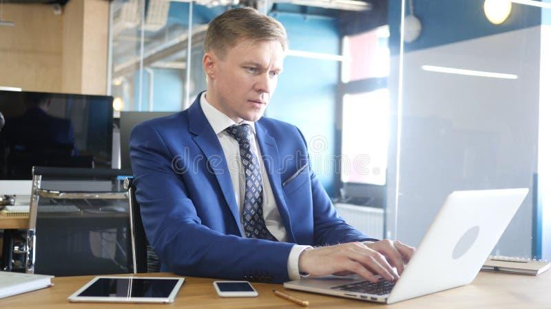 Uomo d'affari Typing sul computer portatile sul lavoro fotografia stock