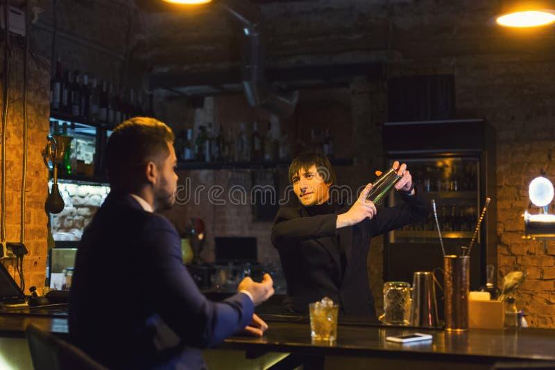 Uomo d'affari ubriaco che parla con barista fotografia stock