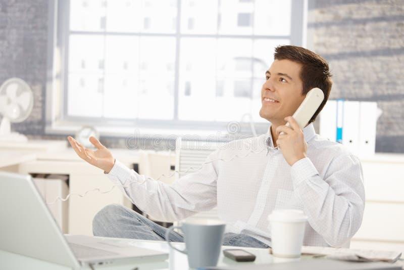 Uomo d'affari in ufficio sulla chiamata di telefono immagini stock